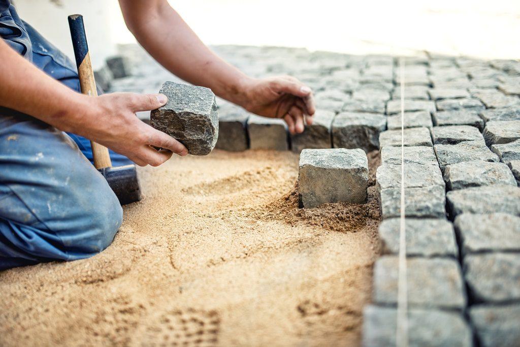 pracownik budowlany umieszczenie kamiennych płytek w piasku na chodniku, taras. Pracownik umieszczający granitowy bruk bruku na lokalnym tarasie